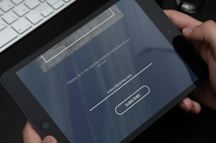 A tablet with a form and a subscribe button on its screen